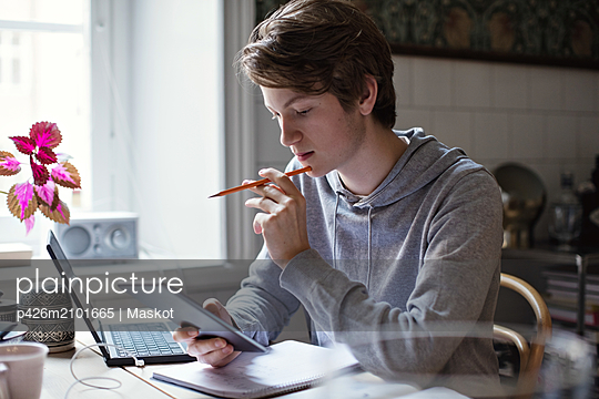 Serious teenage boy using digital tablet while doing homework on table - p426m2101665 by Maskot