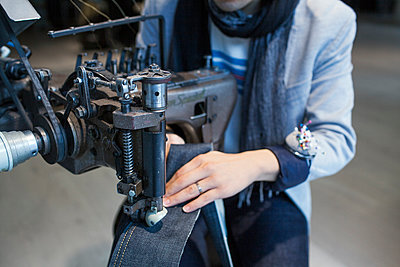 Midsection of male fashion designer using sewing machine in jeans factory - p1185m994338f by Astrakan