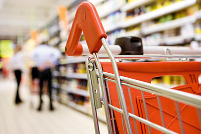 Shopping cart in supermarket, shoppers in background - p623m1487556 by James Hardy