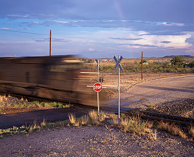 Blurred train on railroad crossing - p644m728443 by Neil Barclay