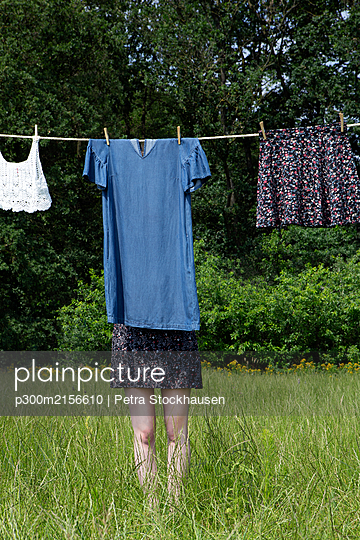 Young woman hiding behind dress drying on clothesline - p300m2156610 by Petra Stockhausen