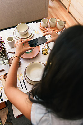 Woman capturing phone photo from overhead of dinnerware display - p1166m2208518 by Cavan Images