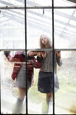 Zwei Mädchen hinter Fensterscheibe - p1348m1480868 von HANDKE + NEU