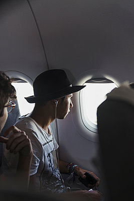 Young man wearing a hat in a plane looking out of window - p300m2042216 by Kike Arnaiz