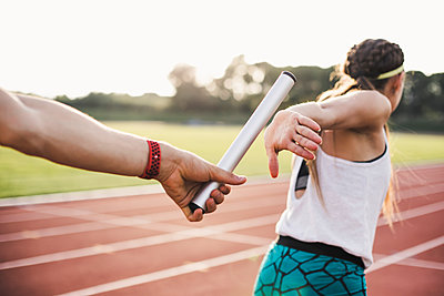Close-up of a athlete passing the baton to a female athlete - p300m2078841 by Aitor Carrera Porté
