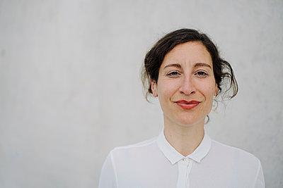 Portrait of a smiling businesswoman at a concrete wall - p300m2198435 by Joseffson