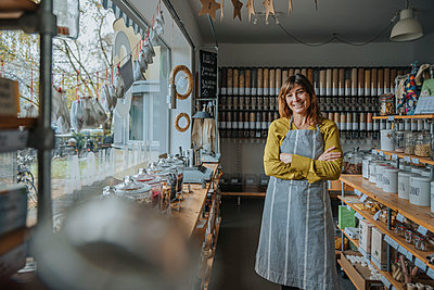 Smiling saleswoman with arms crossed standing in zero waste store - p300m2256464 by Mareen Fischinger