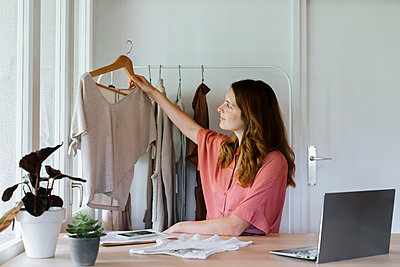 Female fashion designer examining top at home office - p300m2287129 by VITTA GALLERY