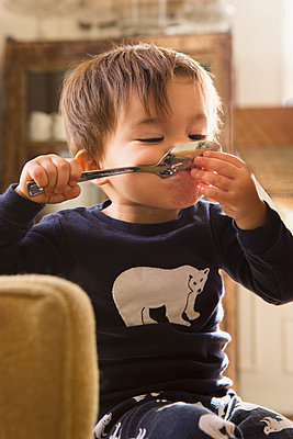 Mixed Race boy holding spoon in mouth - p555m1422281 by Lucy von Held