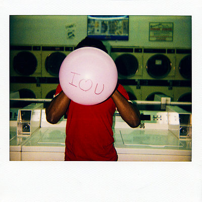 Instant film photograph of man with balloon saying 'I love you' - p9240640 by Adam Hester