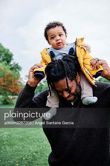 Father carrying son on shoulder in park - p300m2287203 by Angel Santana Garcia