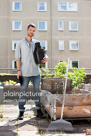 Portrait of young man with stacked flower pots standing at urban garden - p426m747459f by Maskot