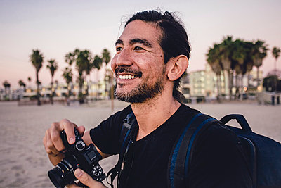 Close-up of smiling backpacker holding camera while looking away at beach - p1166m1556352 by Cavan Images