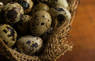 Bird eggs in basket - p1427m2186373 by Tetra Images