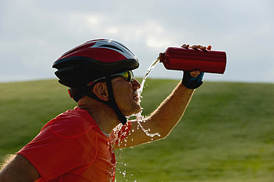 Side view of a cyclist drinking water - p3071155f by Picture  Press, G&L