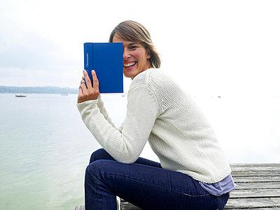 Frau liest Buch auf einem Steg  - p6430082 von senior images