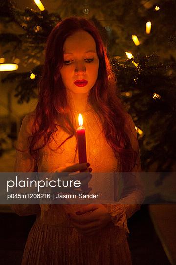 Frau schaut Flamme an - p045m1208216 von Jasmin Sander