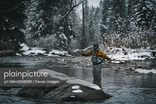 Man fly fishing while standing in river during winter - p1166m2258359 by Cavan Images