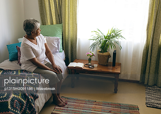 Senior woman sitting on bed at retirement home - p1315m2091186 by Wavebreak