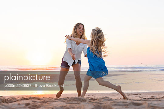 Mother and daughter enjoying while playing at beach during sunset - p300m2243537 by Steve Brookland