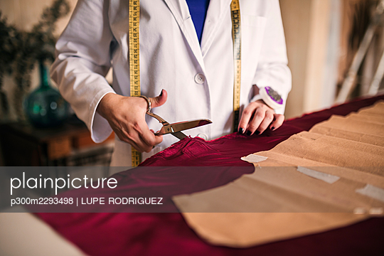 Young female dressmaker cutting maroon silk fabric at workshop - p300m2293498 by LUPE RODRIGUEZ