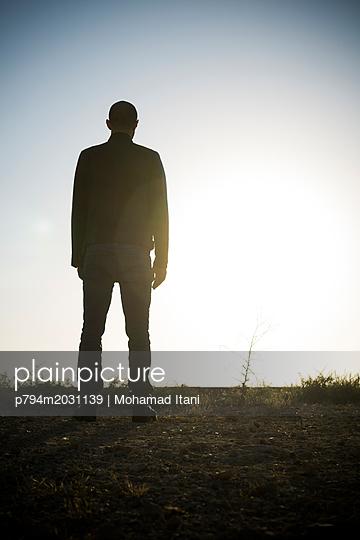 Rückansicht eines einzelnen Mannes in einem Feld - p794m2031139 von Mohamad Itani