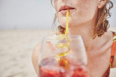 Woman with drink and straw on the beach - p1573m2178916 by Christian Bendel