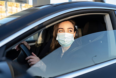 Businesswoman wearing protective face mask looking away while driving car during COVID-19 - p300m2243586 by Jose Carlos Ichiro