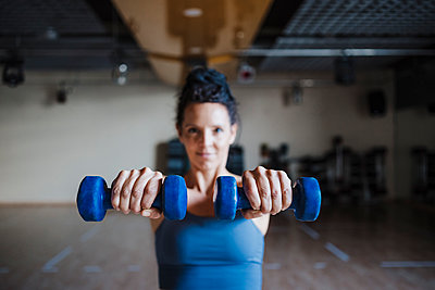 Female sportswoman holding dumbbells in health studio - p300m2265059 by Eva Blanco