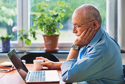 Senior man using laptop at home - p426m1131007f by Maskot