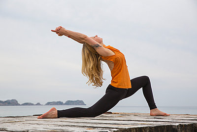 Mid adult woman bending backwards practicing yoga on wooden sea pier - p429m974453f by RUSS ROHDE