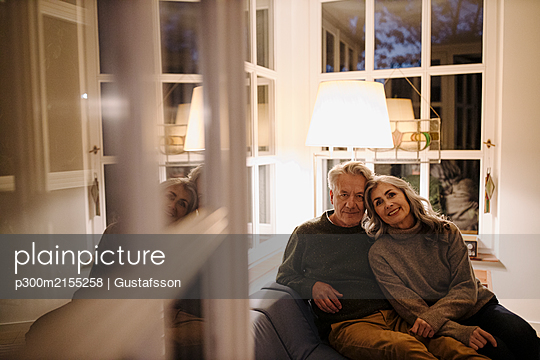 Portrait of senior couple relaxing on couch at home at night - p300m2155258 von Gustafsson