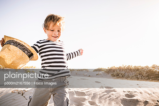 Happy boy with hat running on the beach - p300m2167556 by Floco Images