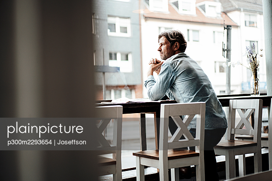 Mature man with hands clasped leaning on table standing in cafe - p300m2293654 by Joseffson