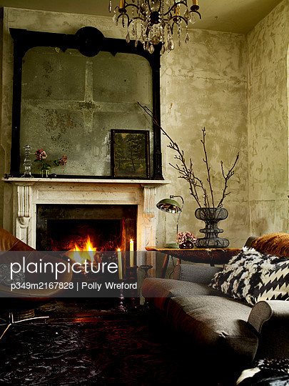 Retro furniture and lit fire with salvaged mirror frame - p349m2167828 by Polly Wreford