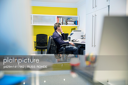 Man sitting at desk in office making telephone call - p429m1417962 by RUSS ROHDE