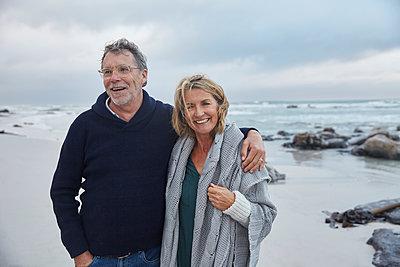 Portrait smiling senior couple hugging on stormy beach - p1023m1217903 by Ryan Lees
