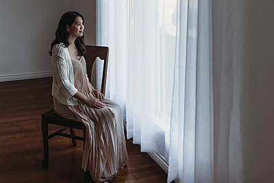 Full length portrait of mother sitting by window in studio - p1166m2131007 by Cavan Images