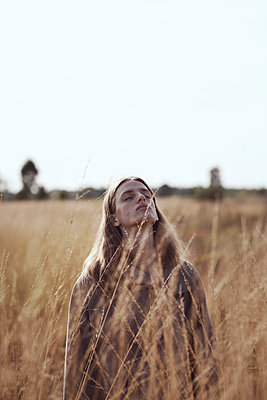Sensual portraits of man with long hair on field - p1561m2133241 by Andrey Cherlat