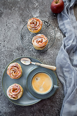 Filo pastry apple cakes in rose shape with cup of coffee - p300m1189055 by Sandra Roesch