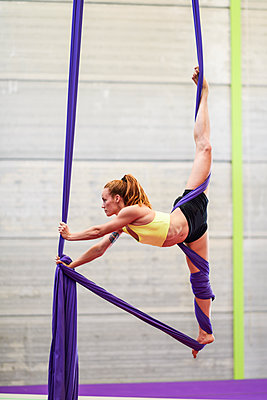 Young woman doing aerial silk in an exercise room - p300m2140678 by Javier Sánchez Mingorance