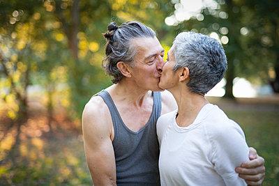 Senior couple kissing in park - p312m2080526 by Viktor Holm