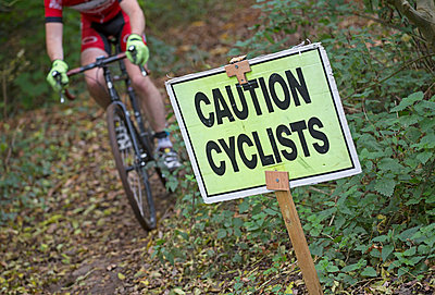 Male Cyclo-cross rider riding in a race past a caution/warning sign in woods. - p343m1006627f by James Silverthorne