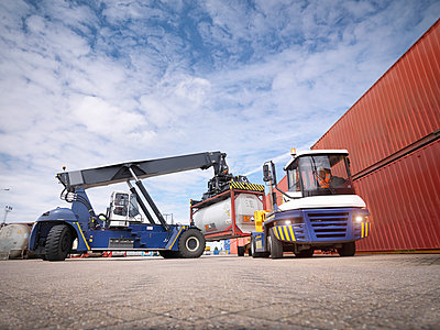 Crane stacking tank containers from truck in port - p429m954627f by Monty Rakusen