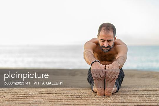 Spain. Man doing yoga on the beach in the evening, stretching legs - p300m2023741 von VITTA GALLERY
