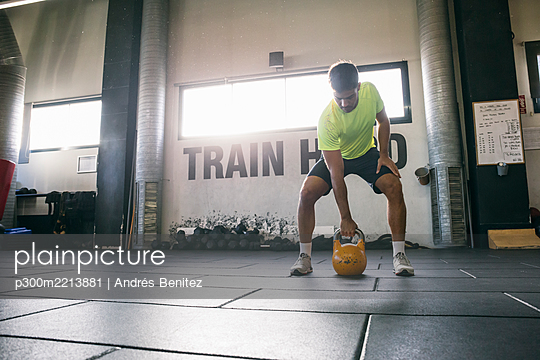 Male athlete lifting kettlebell while standing on floor in health club - p300m2213881 by Andrés Benitez