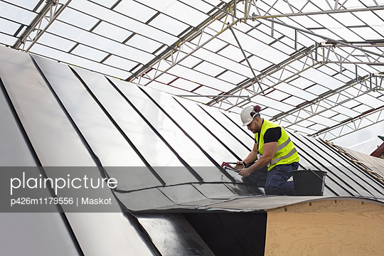 Low angle view of construction worker working on metallic structure at site - p426m1179556 by Maskot