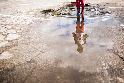 Low section of boy playing in puddle - p1166m1474042 by Cavan Images