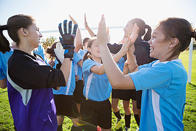 Middle school girl soccer team celebrating high fiving on field - p1192m1173897 by Hero Images