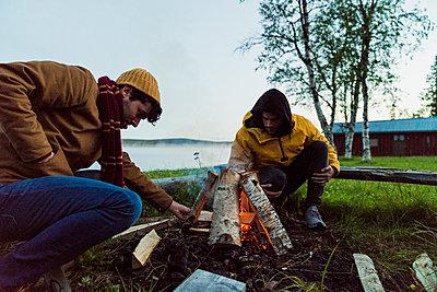 Sweden, Lapland, Two friends preparing a bonfire at the lakeshore - p300m2042295 by Kike Arnaiz